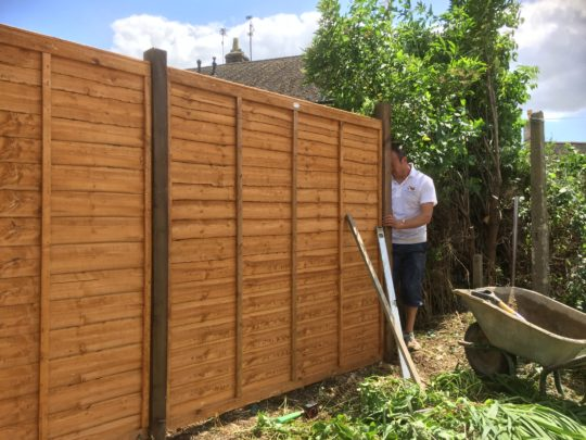 Pauling installing a Waney Fence for a customer in Easton on the Hill