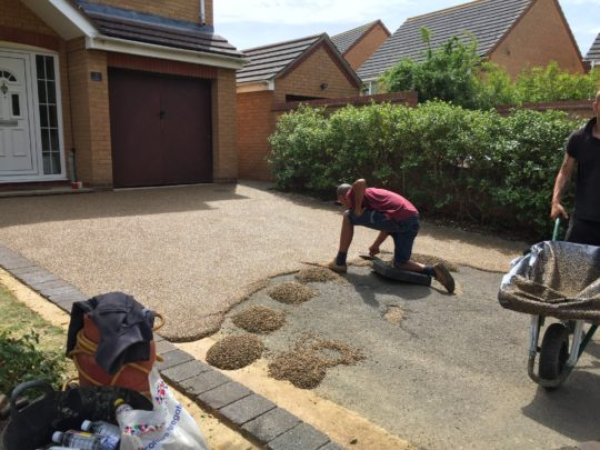Resin being trowelled onto Tarmac